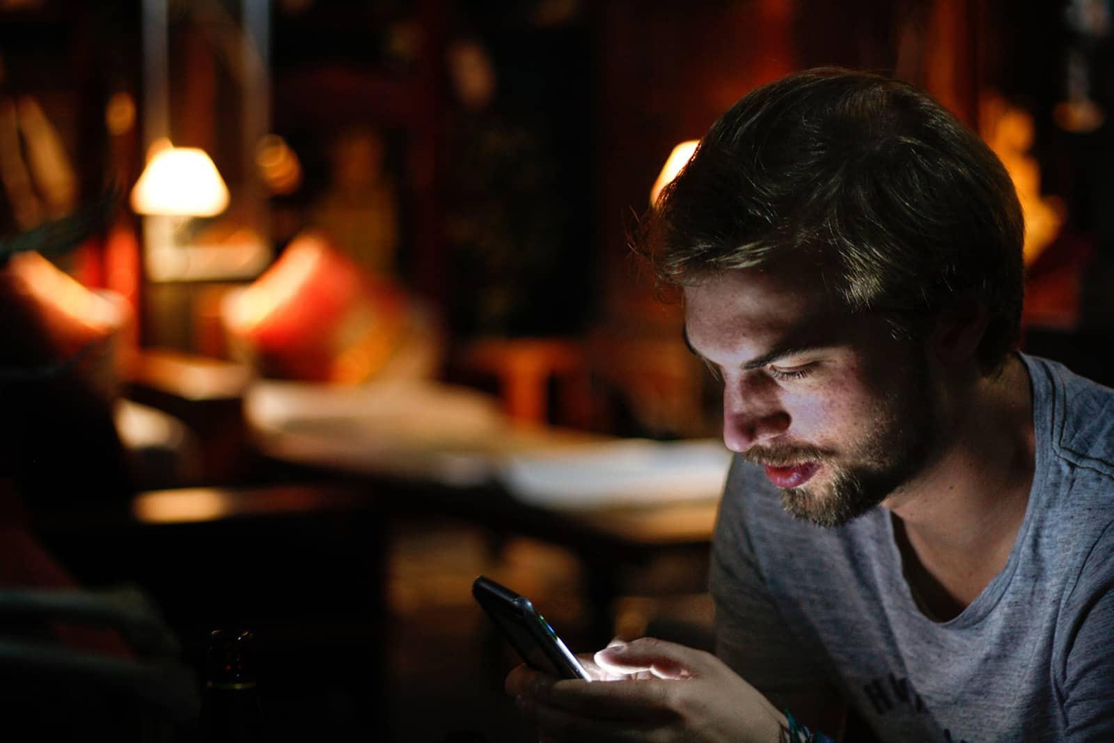 un homme utilisant un smartphone dans le noir à la maison