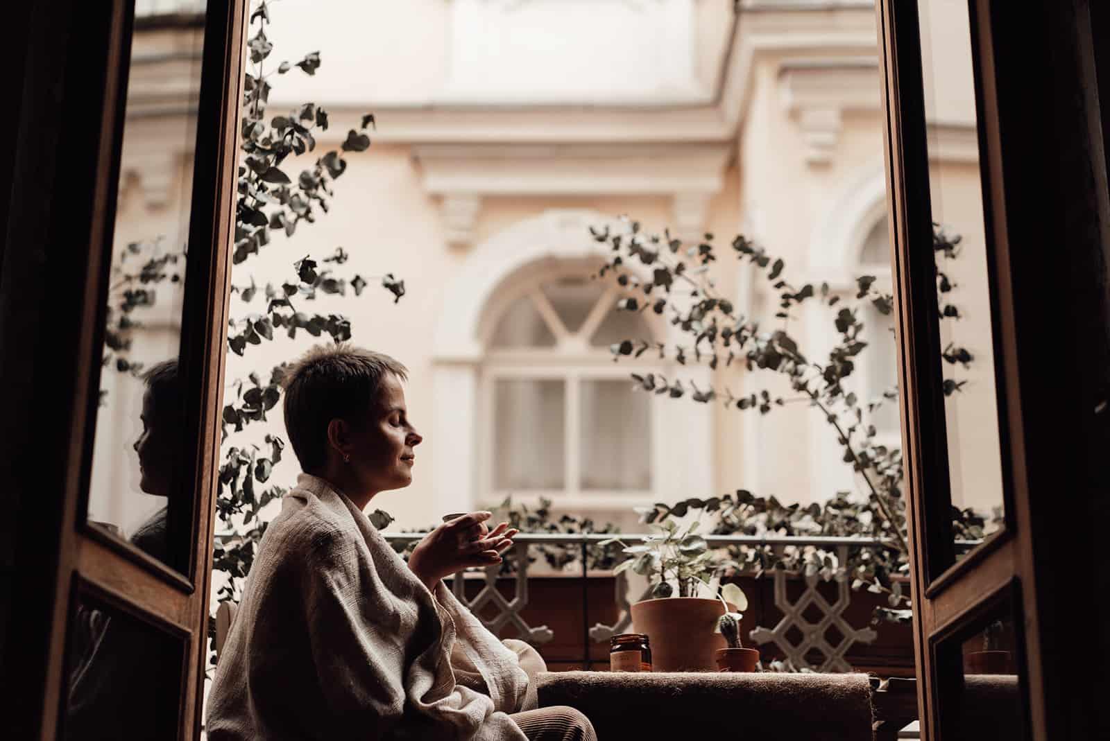une femme aux yeux fermés assis sur le balcon et boire du café