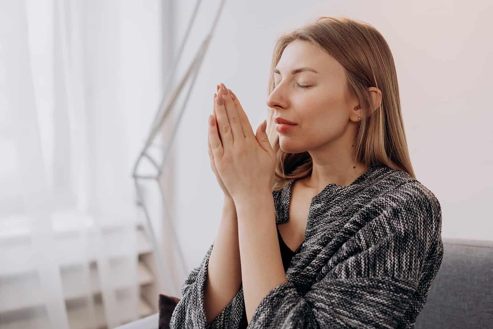 une femme aux yeux fermés méditant à la maison