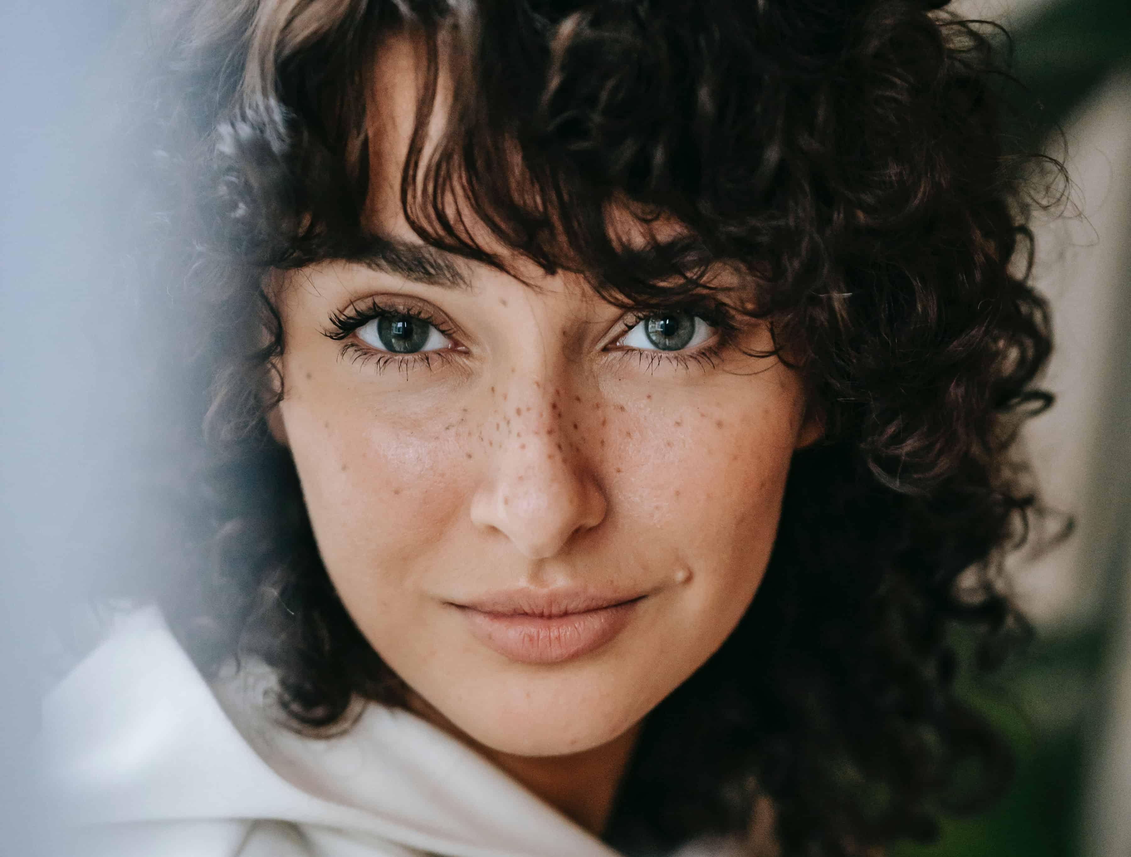 une femme avec des taches de rousseur sur le visage à la confiance