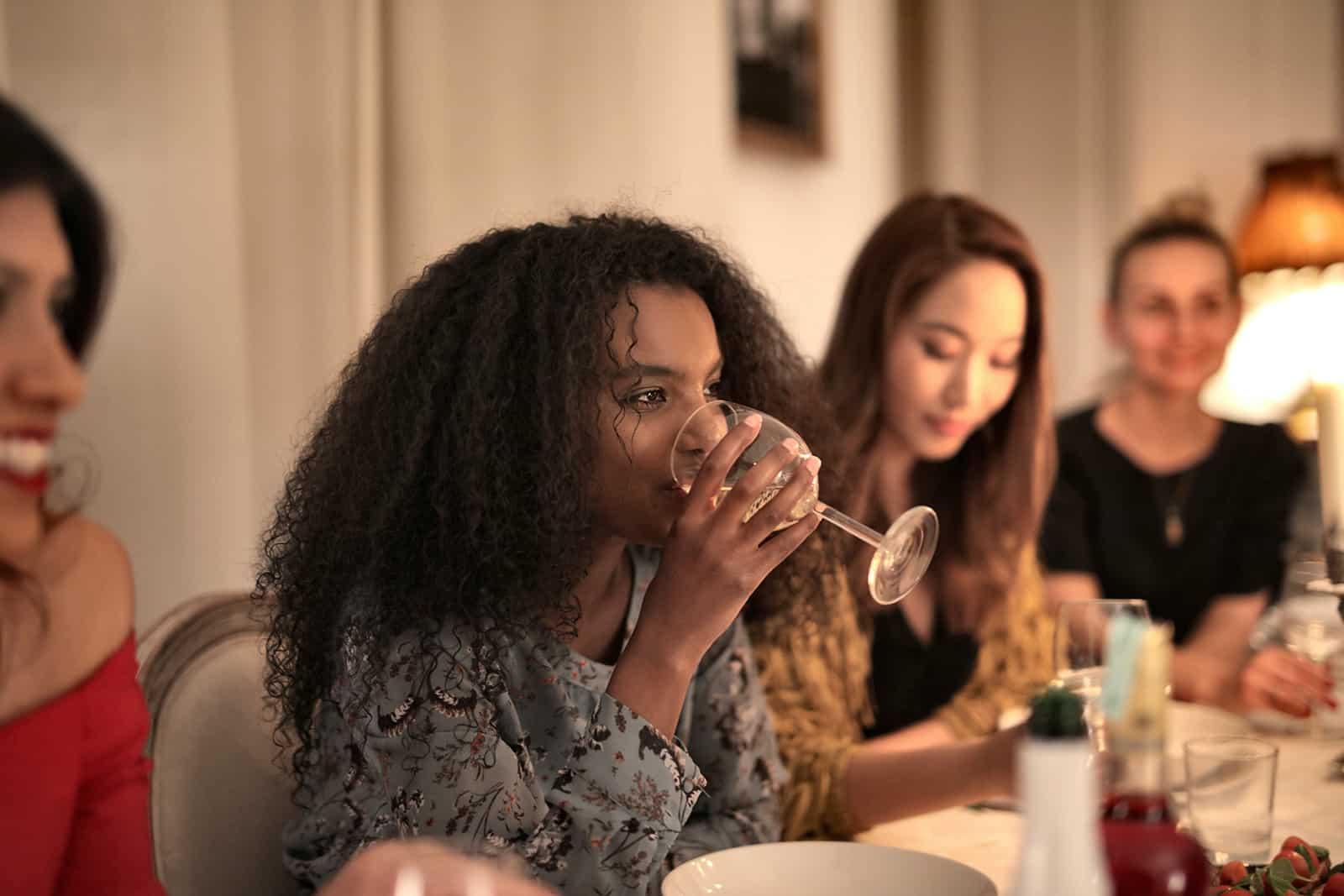 une femme buvant du vin avec des amis au dîner