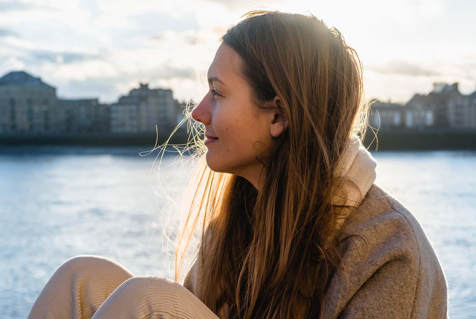une femme calme face à la ville assis près de la rivière