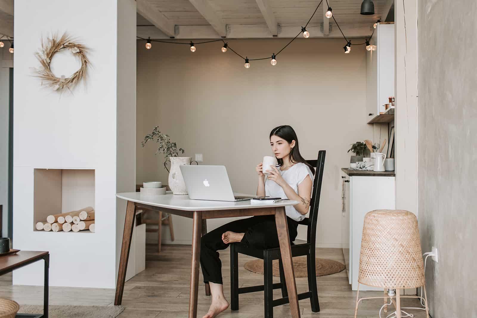 une femme concentrée buvant du café assise à la table devant un ordinateur portable