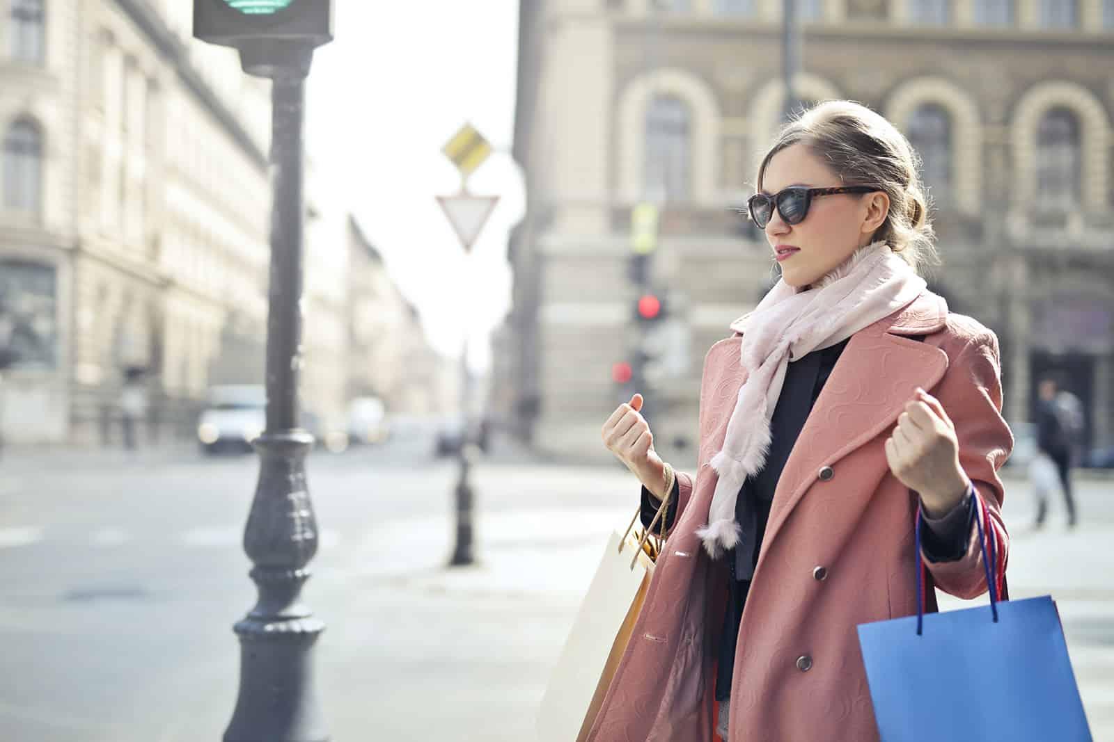 une femme confiante debout dans la rue et tenant des sacs à provisions
