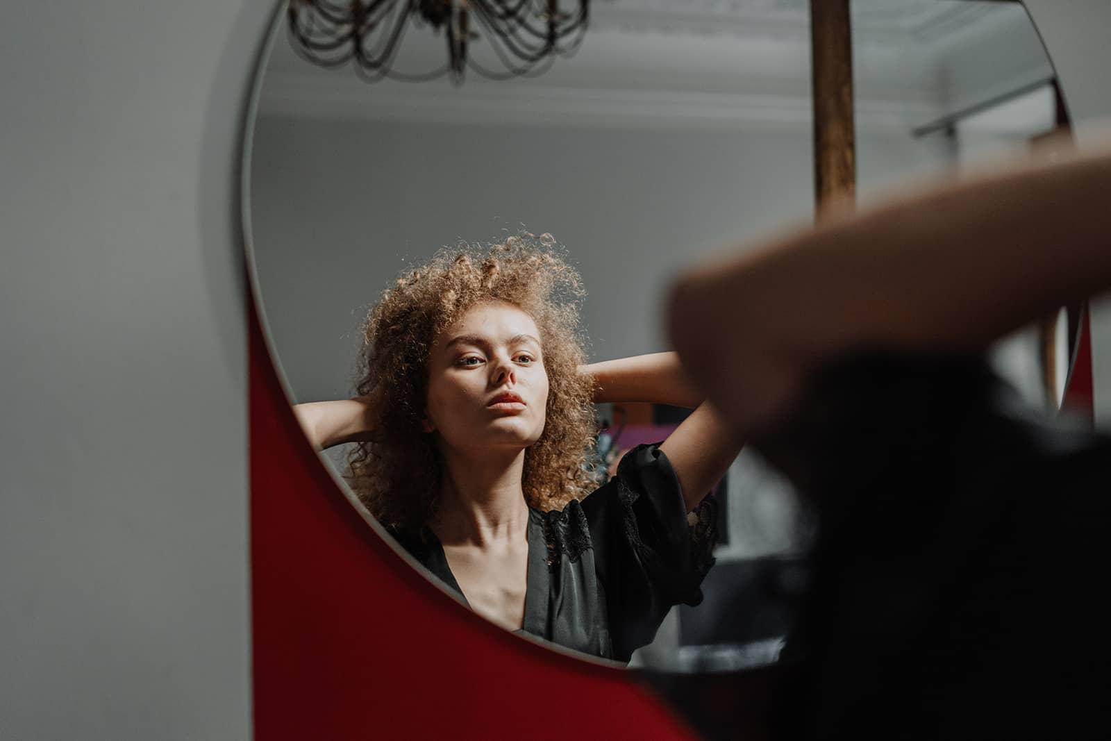 une femme confiante debout devant le miroir et se regardant