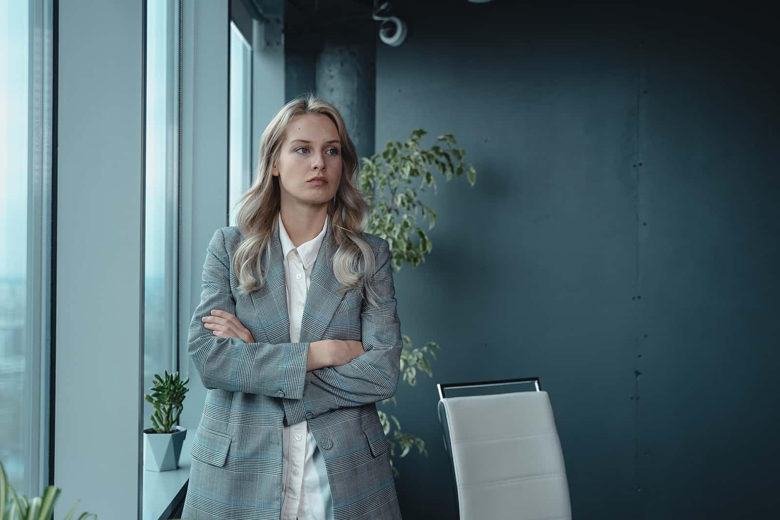 une femme de mauvaise humeur avec les bras croisés debout dans le bureau