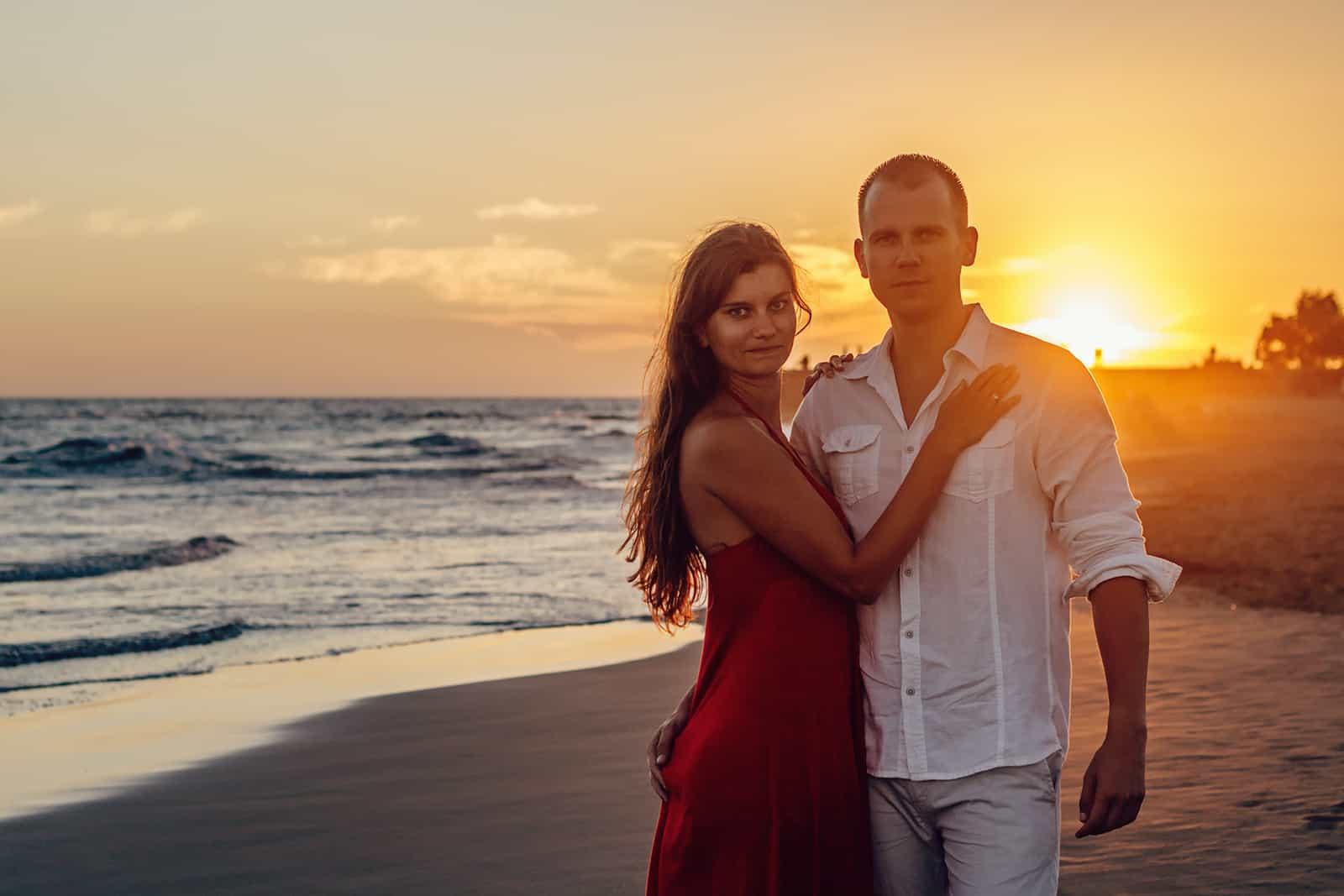 une femme embrassant son homme debout près du rivage