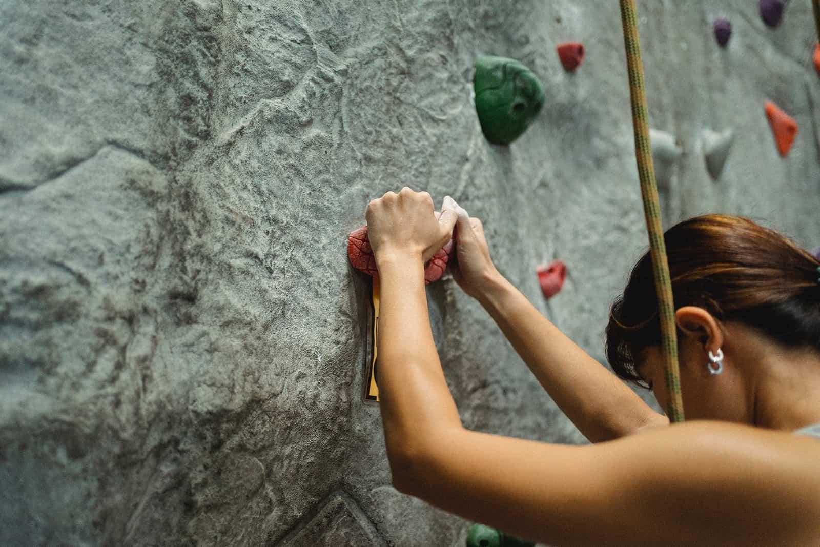 une femme escalade un rocher pendant l'entraînement