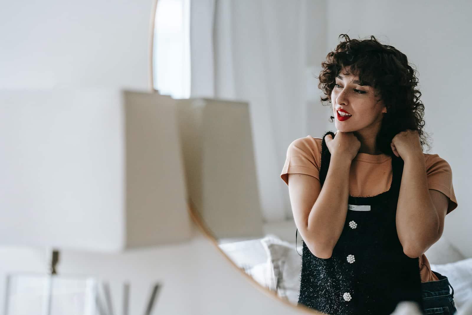 une femme essayant une robe élégante et debout devant le miroir