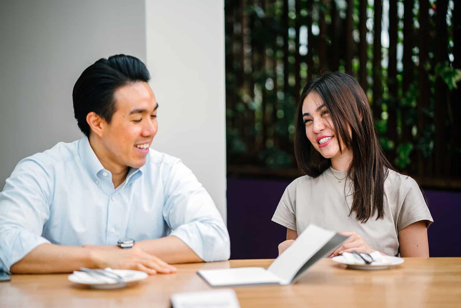 Une femme aimable parlant avec un collègue assis à la table ensemble