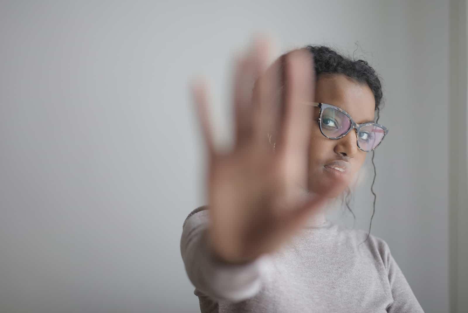 une femme levant la main faisant un geste d'arrêt