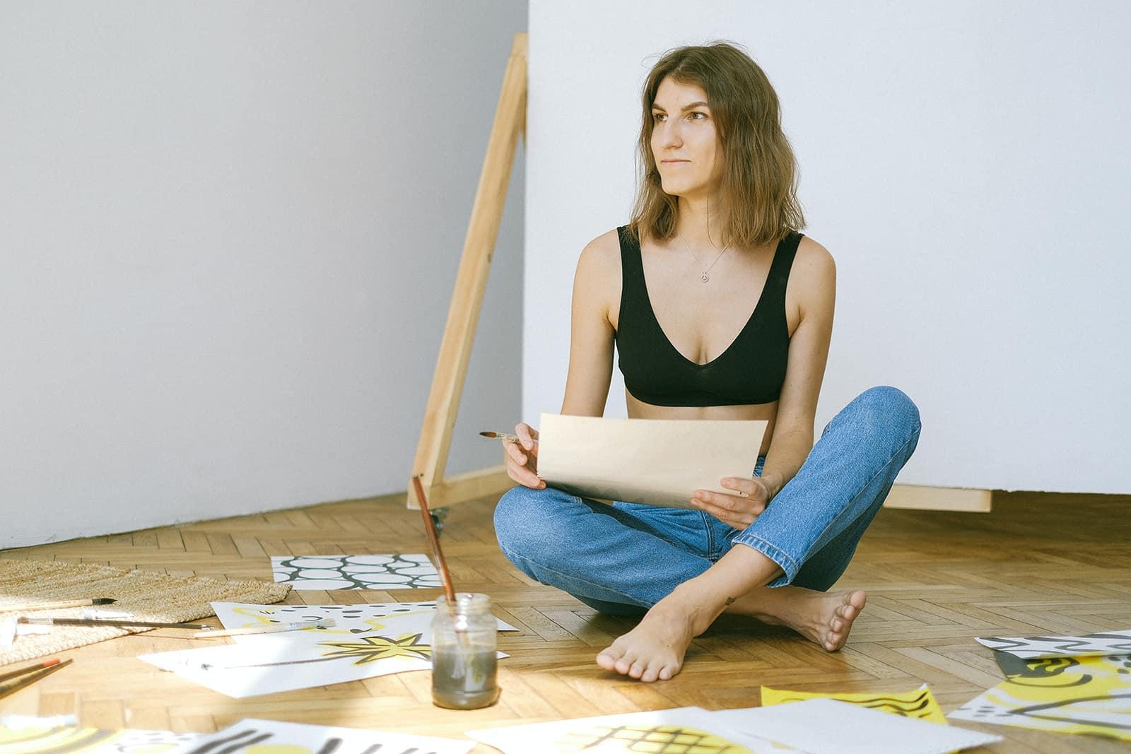 une femme peinture sur papiers assis sur le sol