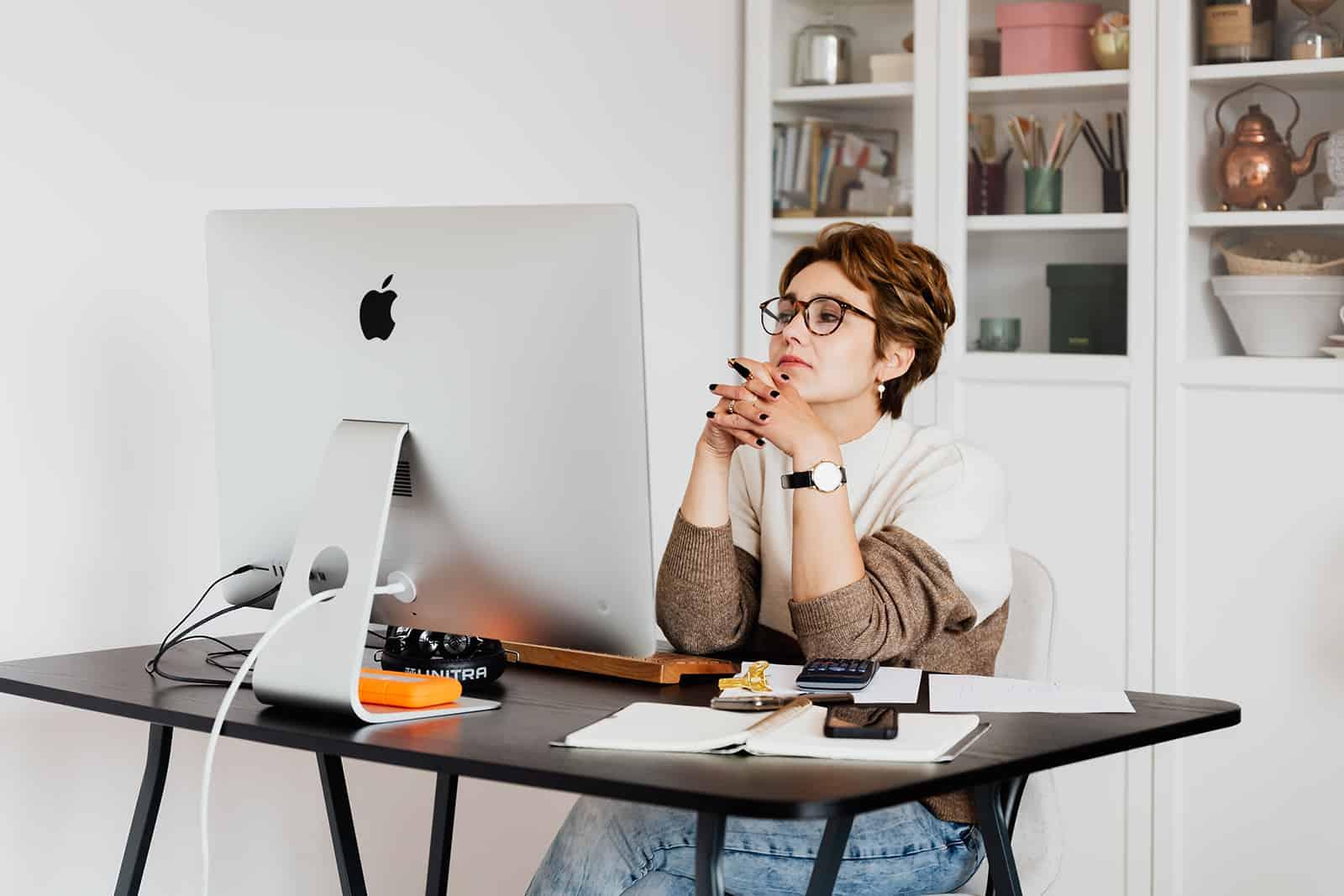 une femme pensive assise dans le bureau et regardant un ordinateur