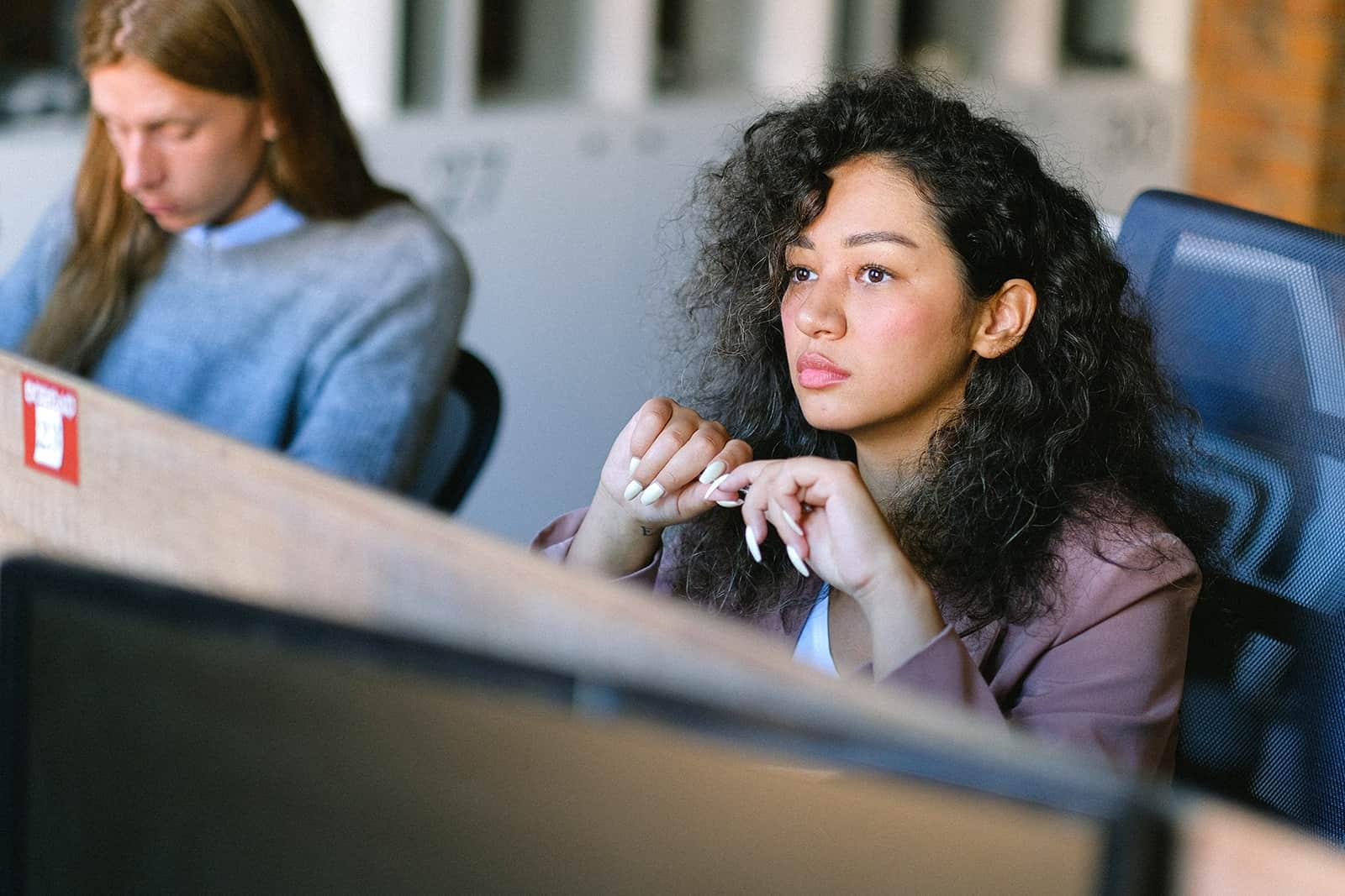 Une femme pensive assise sur le lieu de travail et regardant droit