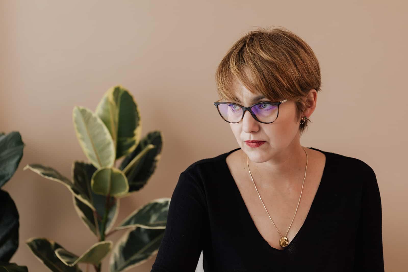 une femme pensive avec des lunettes à côté