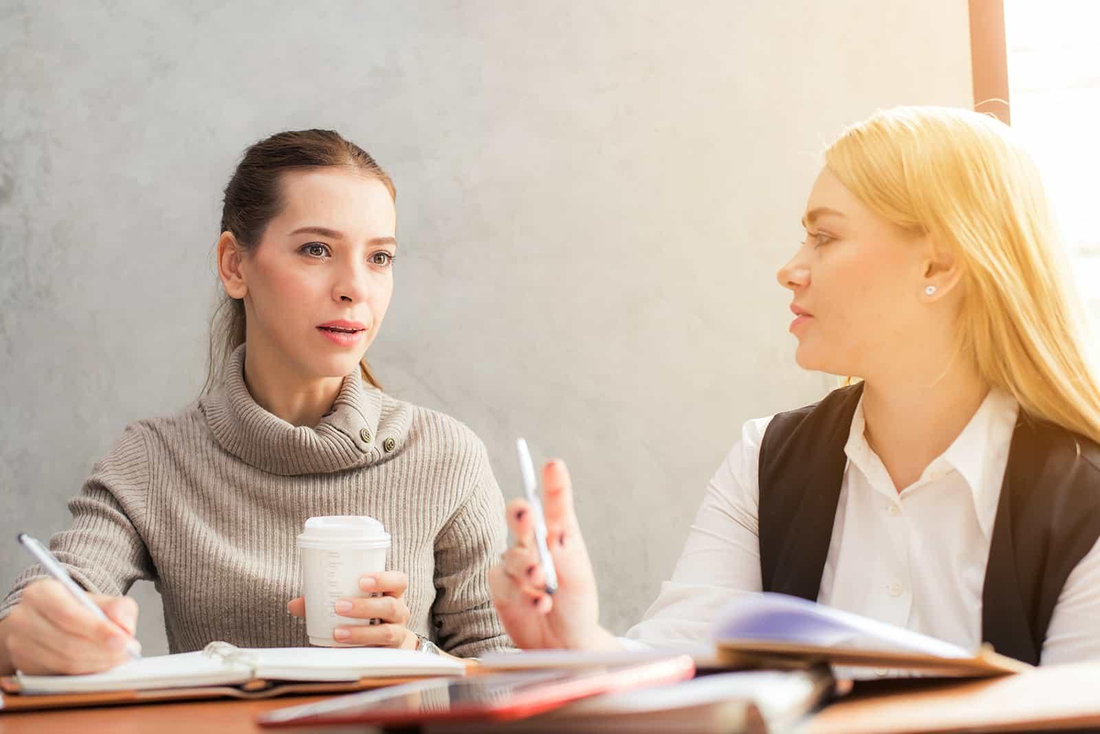 une femme pensive parlant avec une collègue tout en travaillant ensemble
