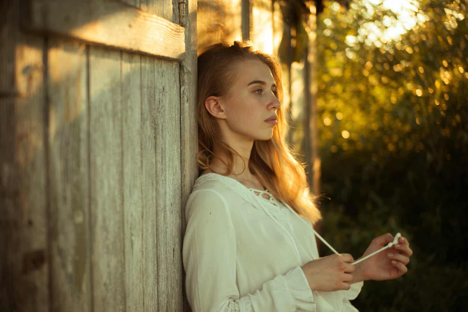 Une femme pensive à la recherche de loin appuyé sur un mur en bois