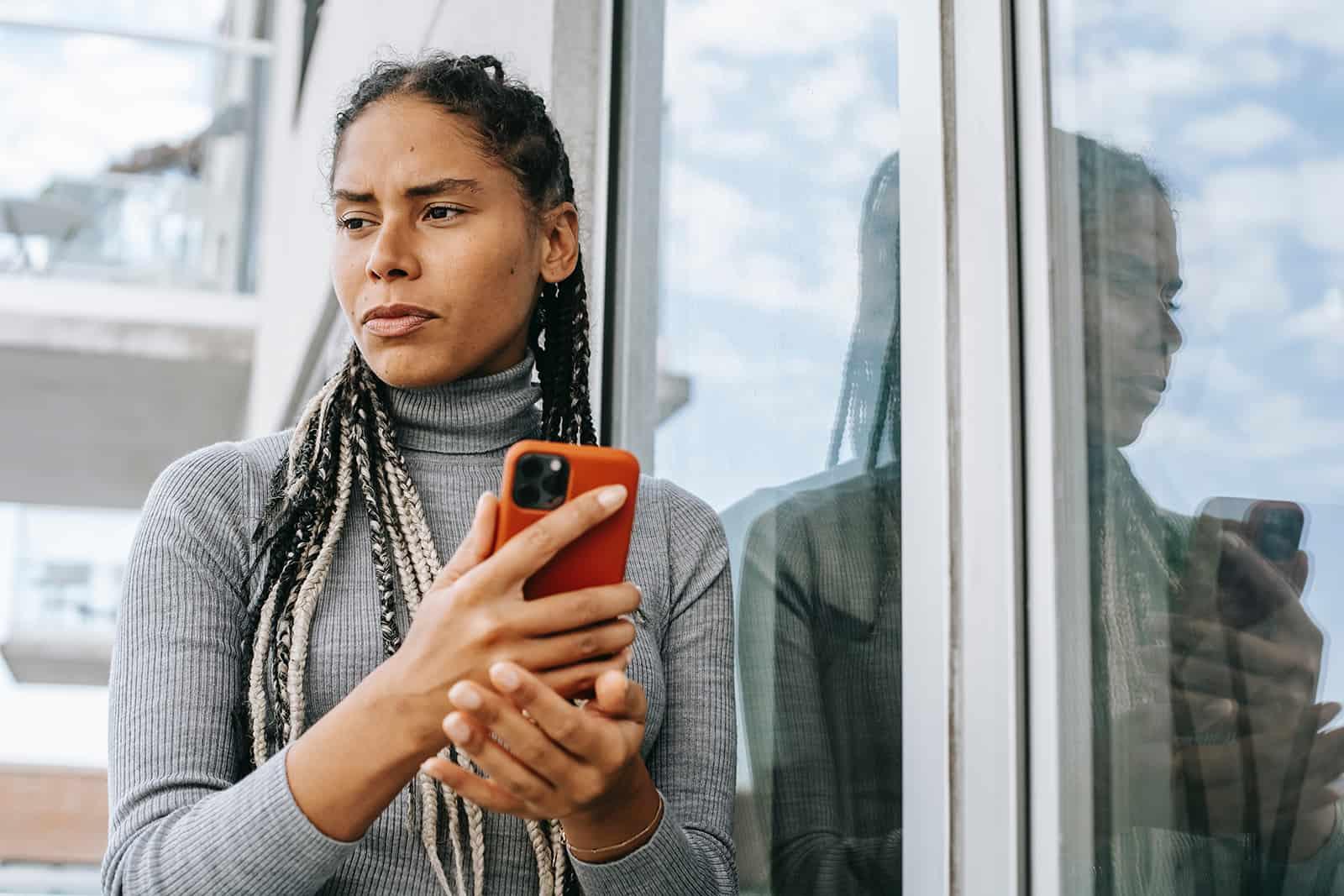 Une femme pensive tenant un smartphone en se tenant debout sur le balcon