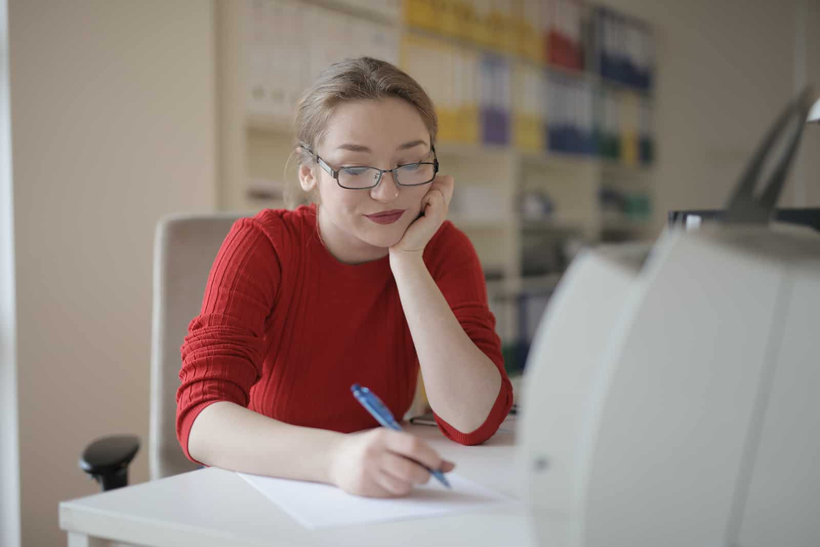 Une femme positive écrivant sur un papier assis au bureau