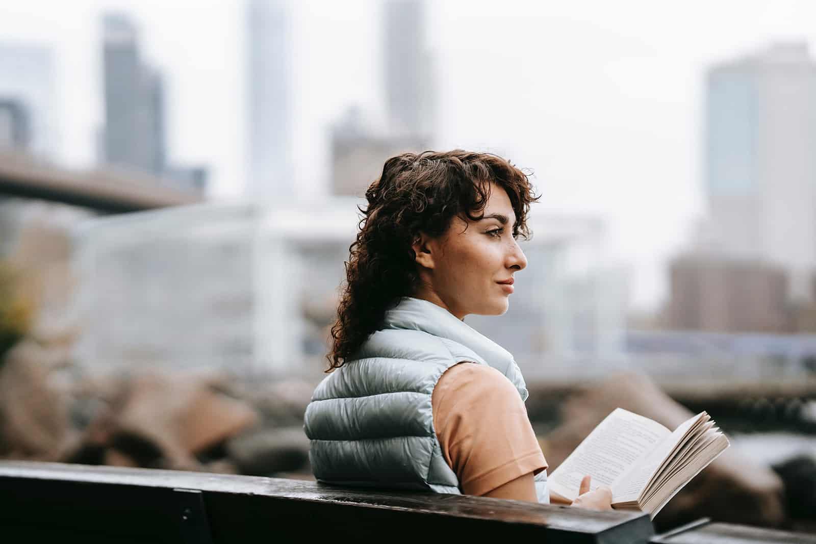 une femme positive lisant un livre sur le banc