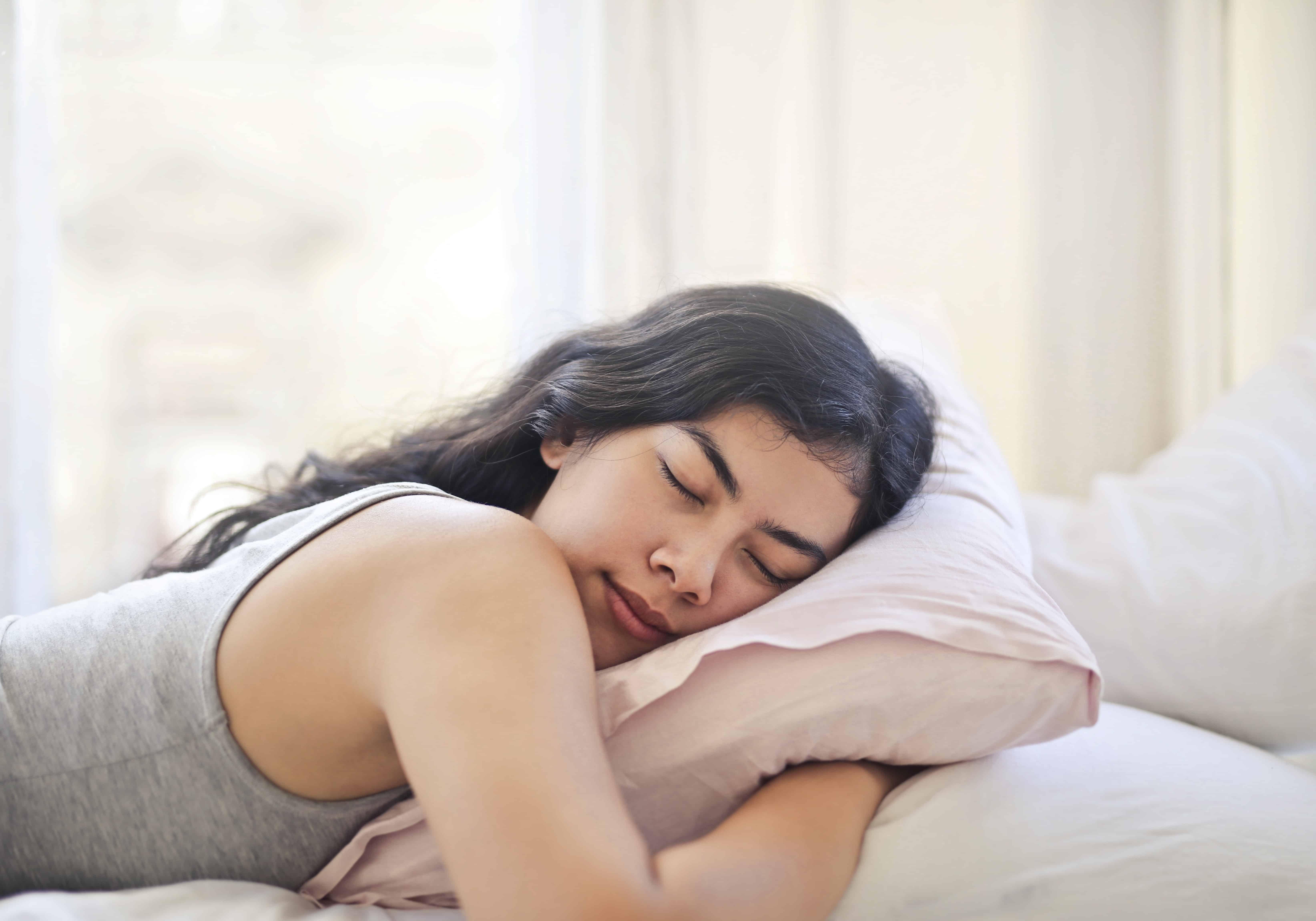 une femme endormie dans le lit et serrant un oreiller