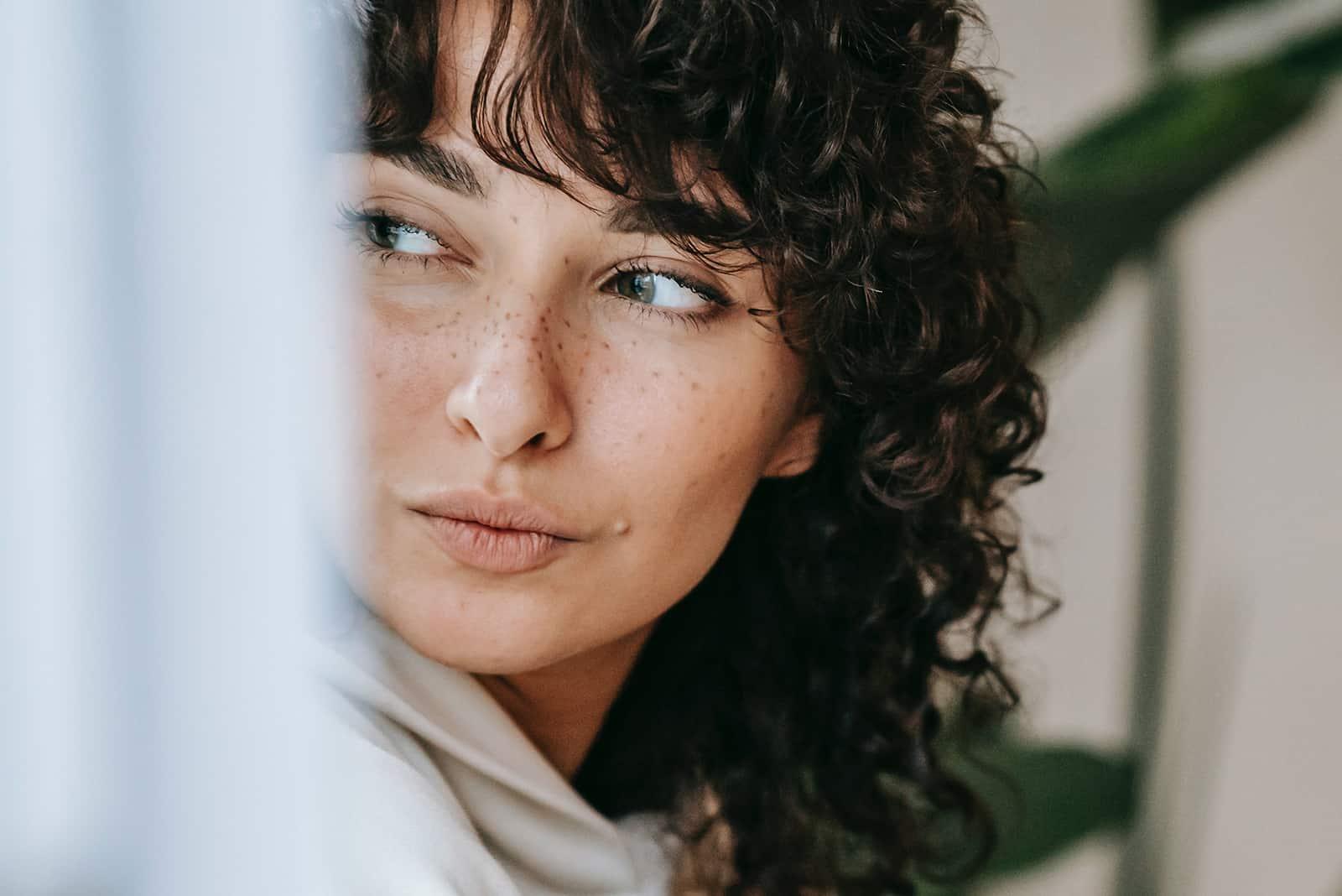 une femme rêveuse aux cheveux bouclés regardant ailleurs
