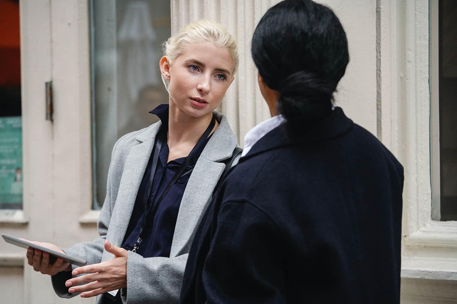 Une femme sérieuse parlant avec son collègue tout en se tenant dehors ensemble