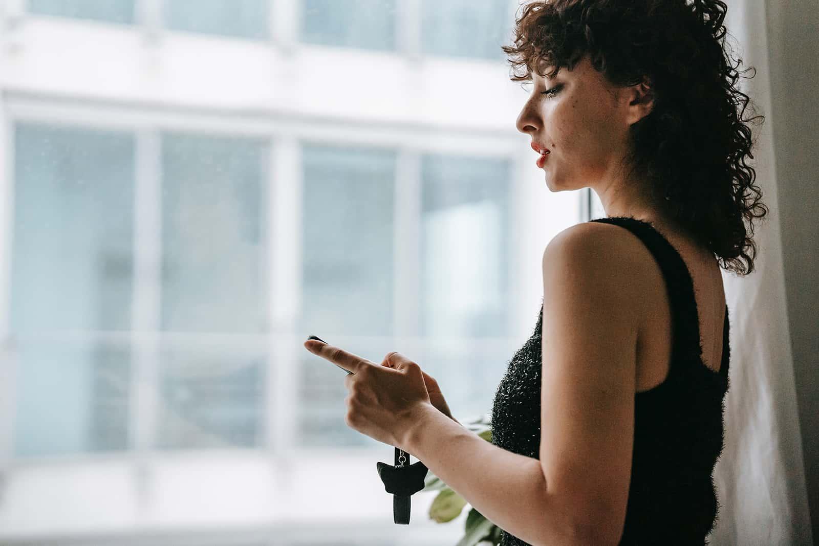 une femme sérieuse regardant smartphone en se tenant près de la fenêtre