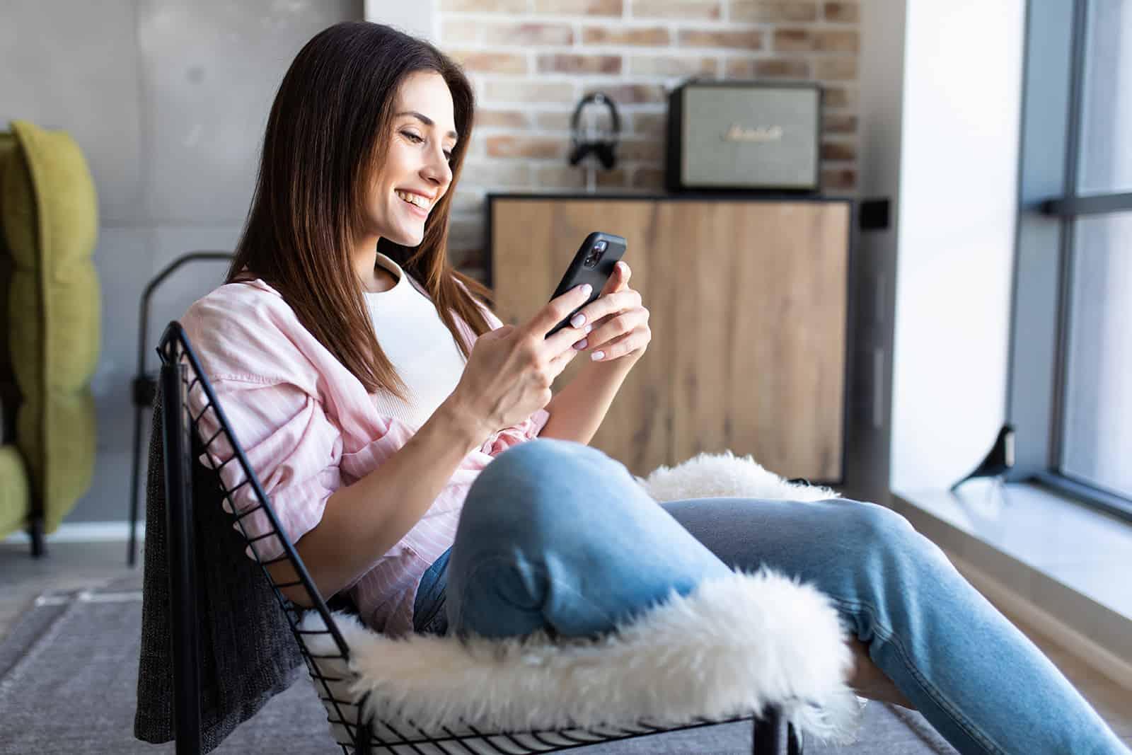 une femme souriante avec téléphone portable assis sur une chaise à la maison