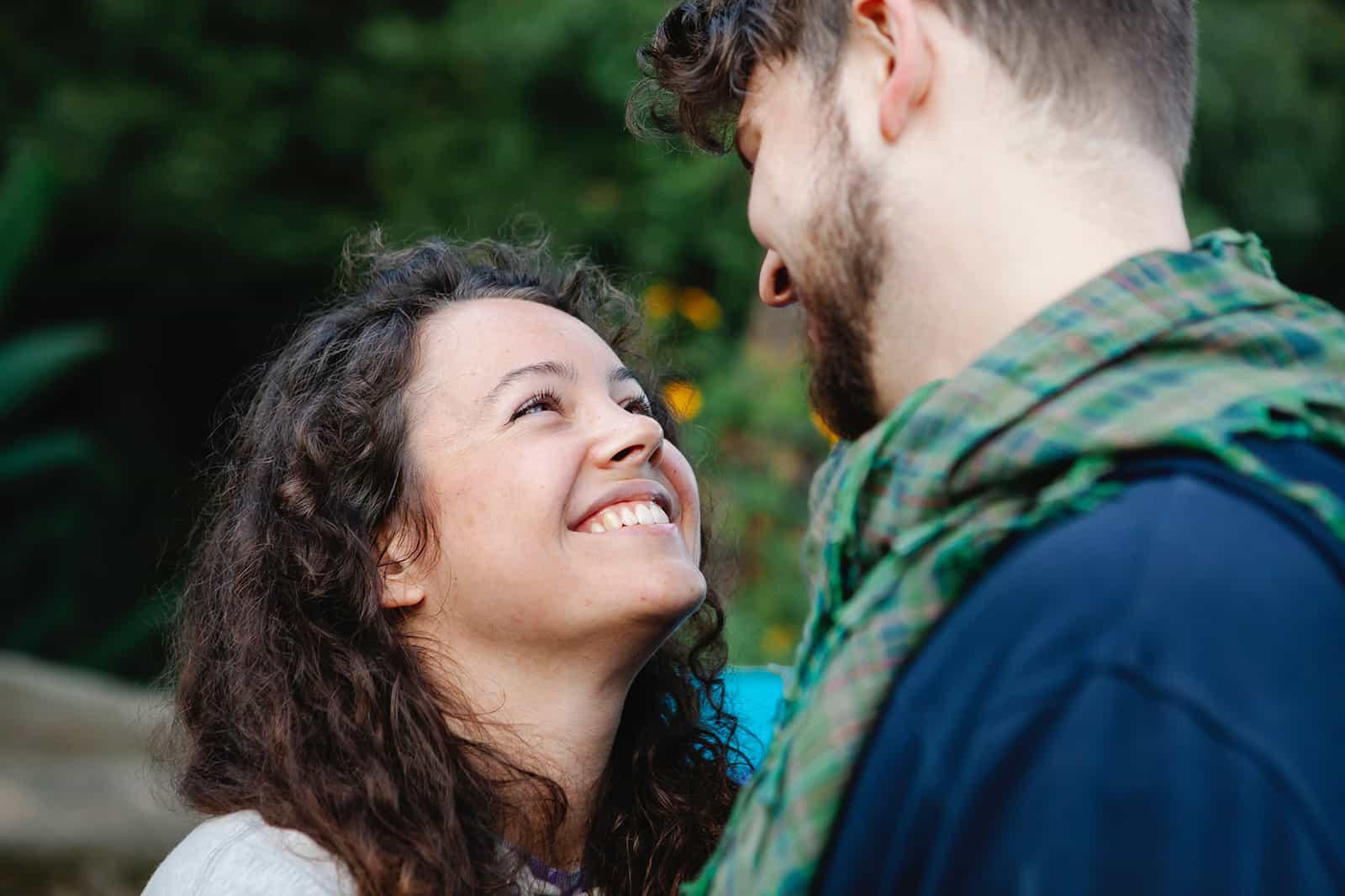 Une femme souriante regardant son petit ami tout en se tenant près de l'autre