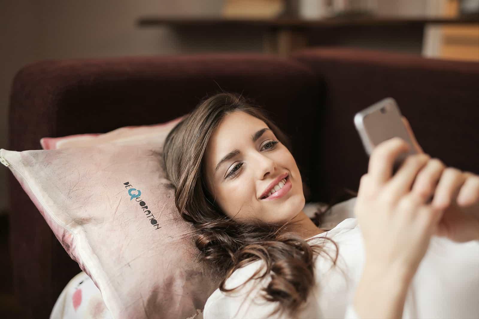 Une femme souriante lisant un message sur un smartphone en position couchée sur le canapé