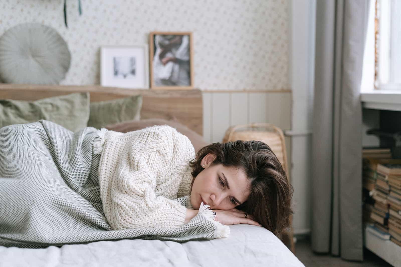 une femme triste allongée sur le lit se sentant déprimée