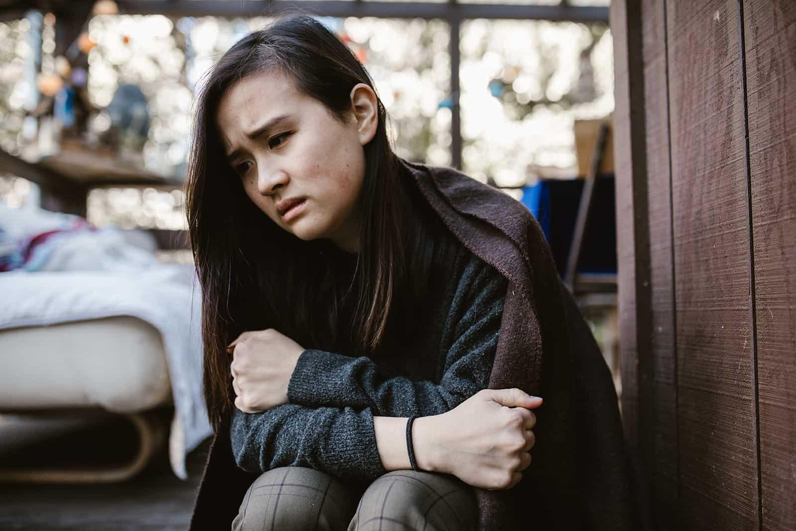 une femme triste couverte de couverture assise sur la terrasse