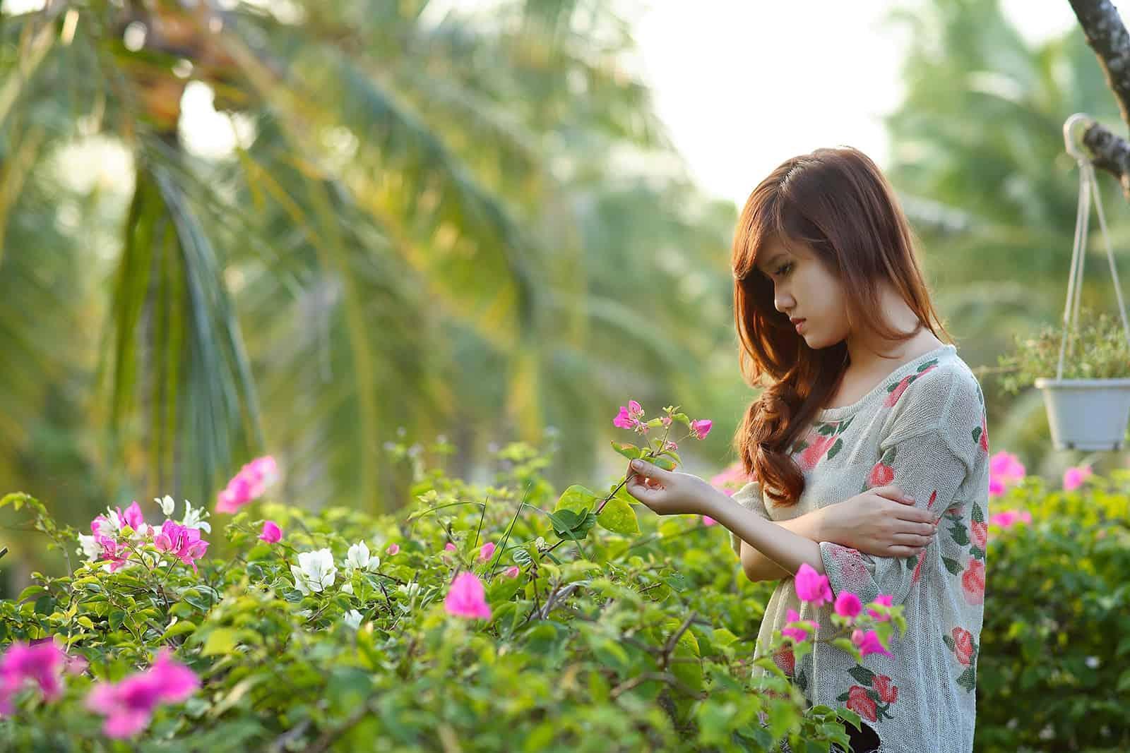 une femme triste debout dans le jardin et toucher des fleurs