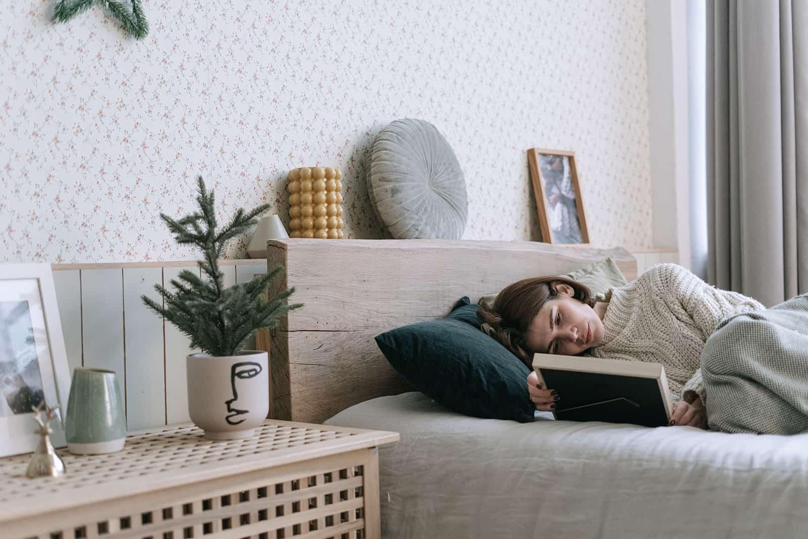 Une femme triste regardant la photographie en position couchée dans le lit