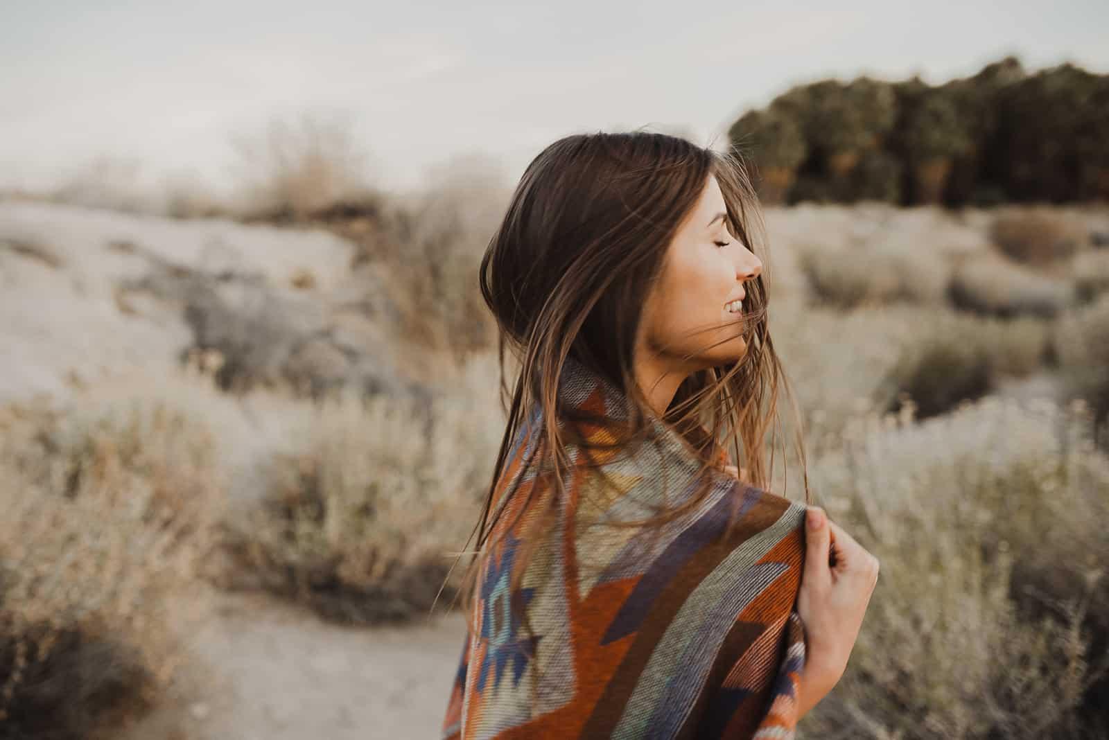 une fille couverte d'une couverture dans la nature