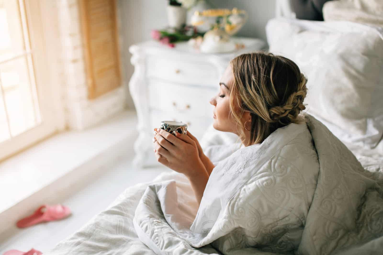 une fille enveloppée dans une couette aime le café