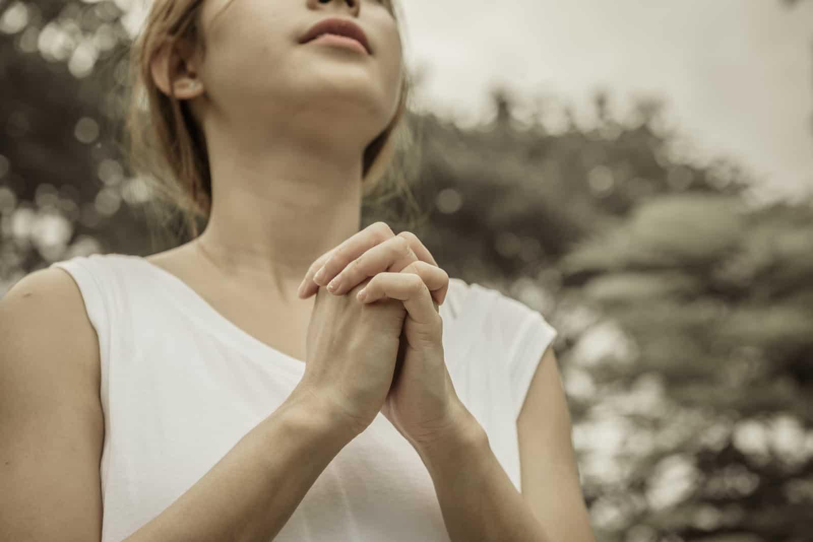 une fille priant dans le parc