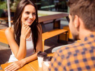 un homme et une femme souriants sont assis à une table et parlent