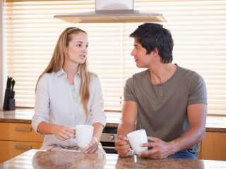 un homme et une femme dans la cuisine sont assis en train de boire du café et de parler