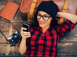 Vue de dessus de la belle jeune femme en couvre-chef allongé sur le sol tenant un téléphone mobile et souriant