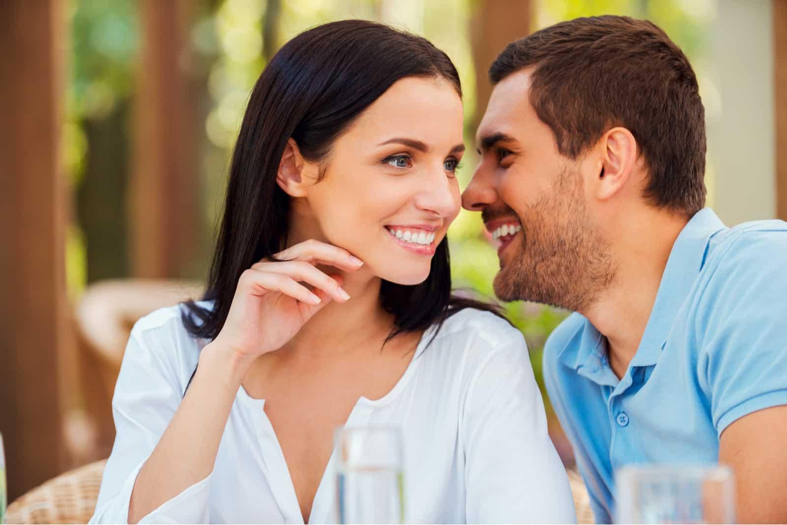 Beau jeune homme disant quelque chose à sa petite amie et souriant alors qu'il était assis à la table à l'extérieur ensemble