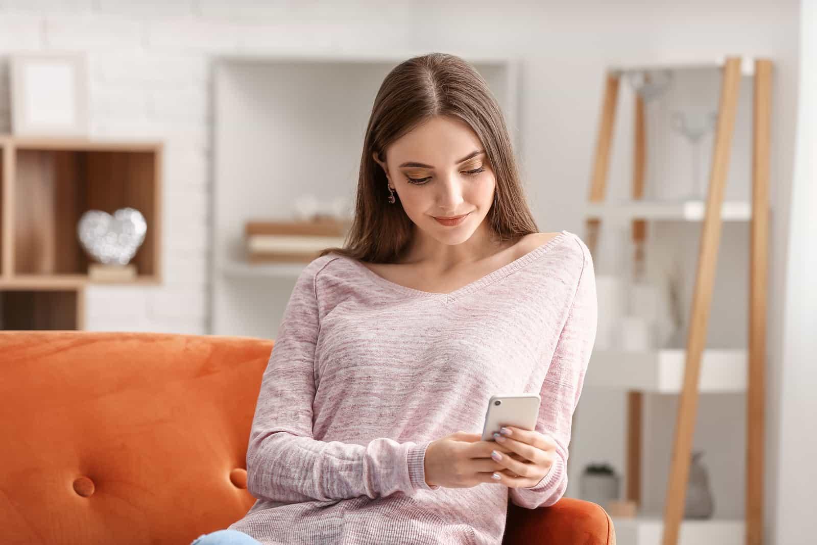 Belle jeune femme avec téléphone portable à la maison