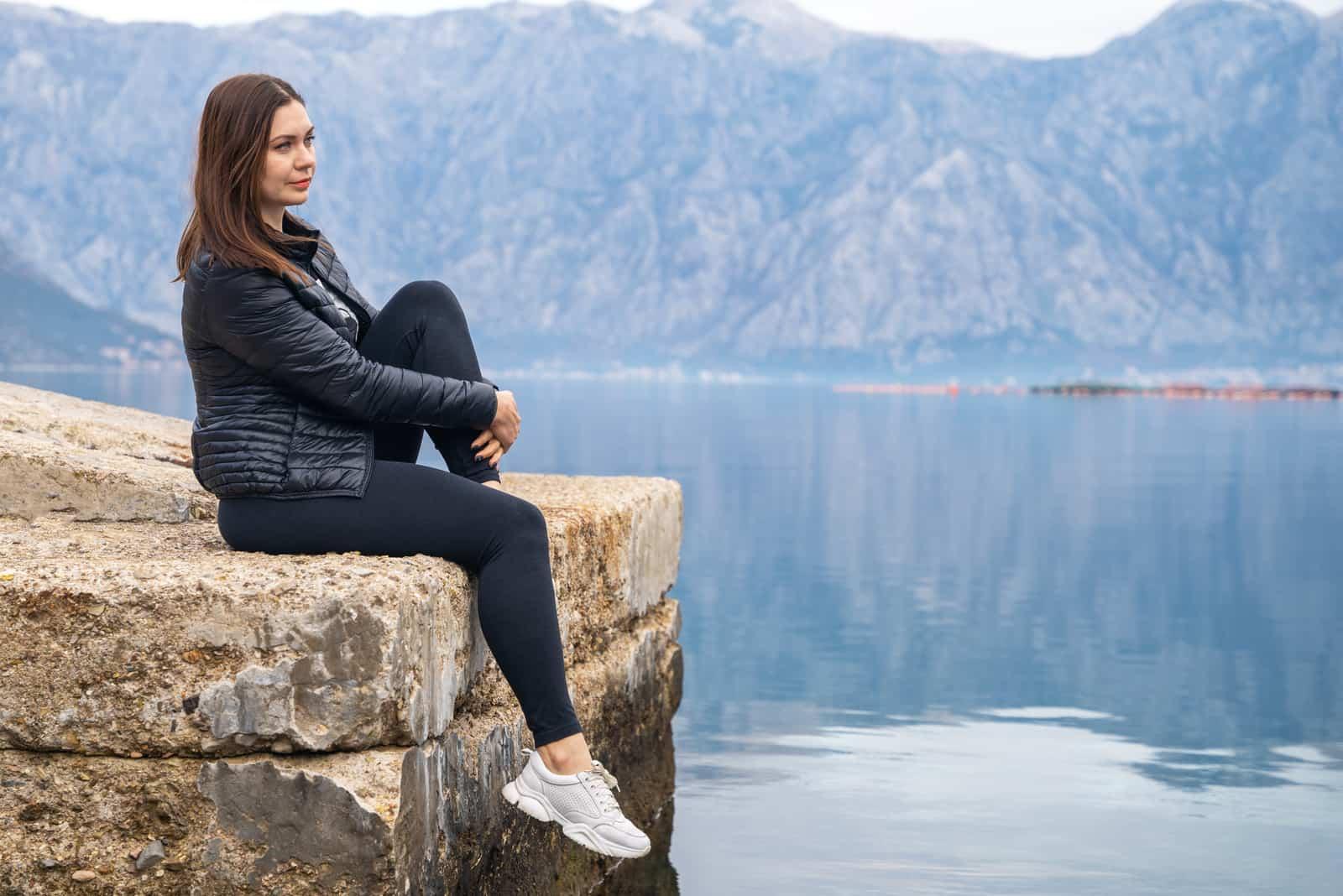 Belle jeune femme brune est assise sur la jetée de pierre et regarda pensivement la mer