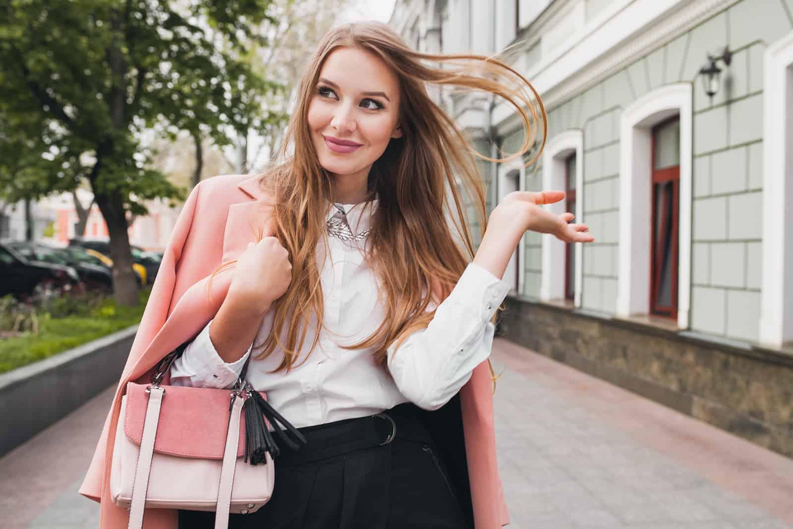 Belle jeune femme élégante marchant en manteau rose, tenant le sac à main dans les mains, souriant