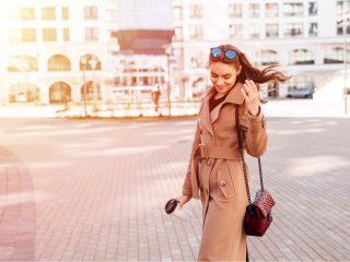 Enthousiaste à la mode jeune femme tenant un café en plein air marchant dans la rue