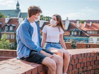 un homme et une femme avec des masques s'assoient sur le mur et parlent
