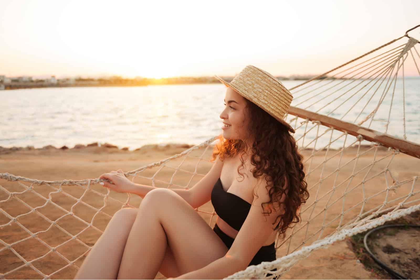 Femme de détente dans le hamac sur la plage tropicale, chaude journée ensoleillée