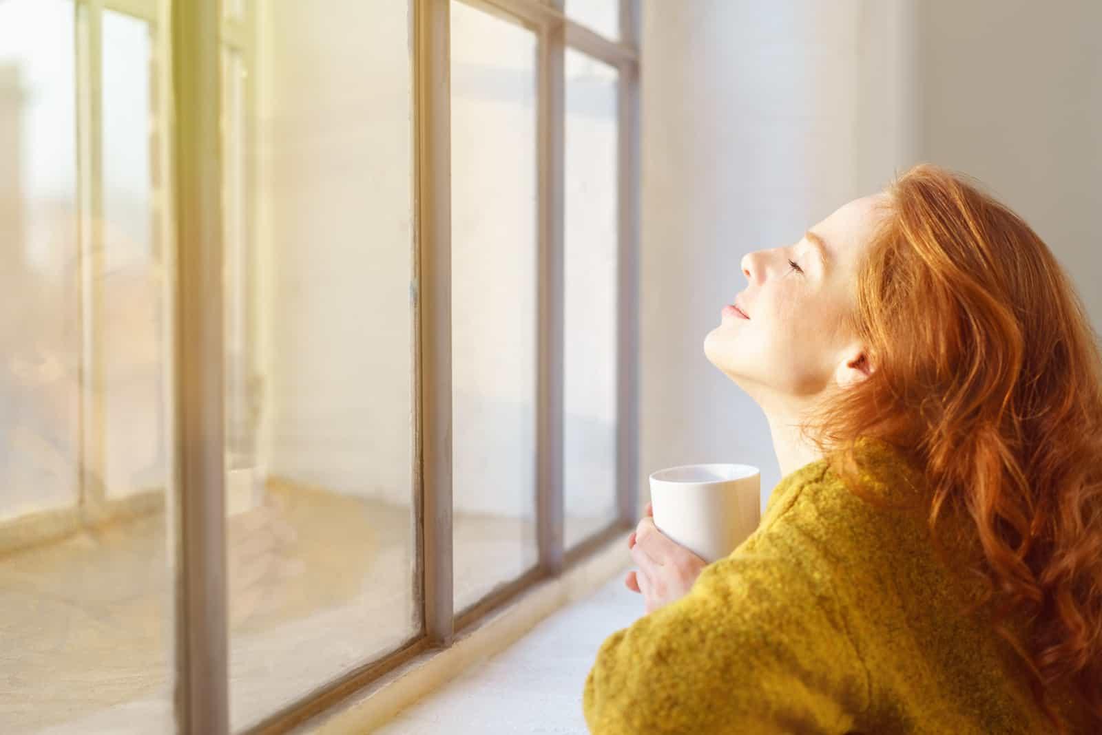 Jeune femme profitant du soleil sur son visage alors qu'elle s'appuie sur un rebord de fenêtre avec sa tête inclinée en arrière et une tasse de café