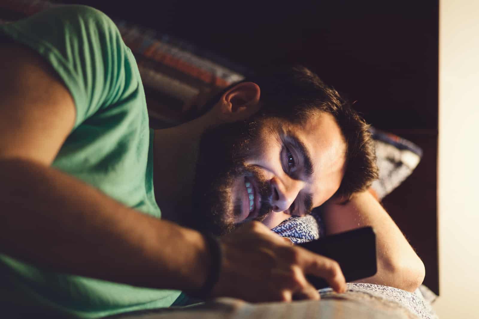 Jeune homme à l'aide d'un smartphone dans son lit la nuit